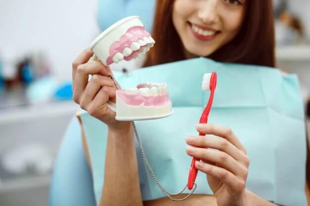 Moça segurando um molde de uma arcada dentária
